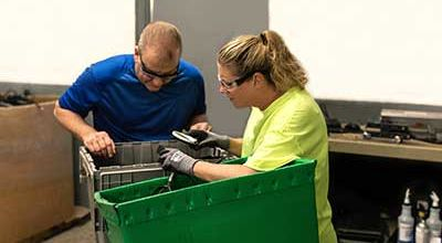 A man and woman looking into a recycling bin