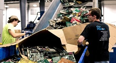 Two men sorting electronics for recycling