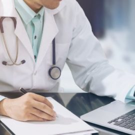 Doctor taking notes from a laptop.