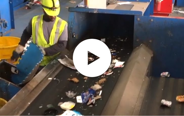 Worker sorting scrap on a conveyor line.